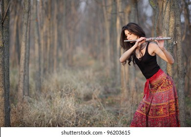 Happy pretty girl in forest playing flute