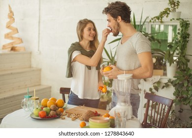 happy pretty girl giving a grape for her boyfriend while preparing drink. happy mood in the kitchen.care