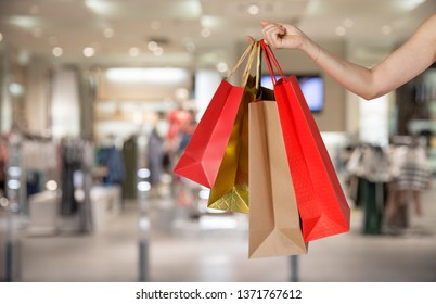 Happy pretty girl holding shopping bags in the shopping mall blurred background, E-commerce digital marketing lifestyle concept