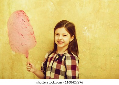 Happy, pretty girl, small, little, child in plaid dress smiling with tasty, pink, cotton candy, sweet, sugar, spun candyfloss, on stick on beige background. Unhealthy food or snack
