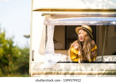 Happy pretty girl in the van are traveling. Unforgettable trip with friends, freedom is your way of life. Open the world again