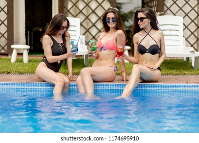 Happy pretty girls with beverages on summer party innear the pool resort. full length photo.