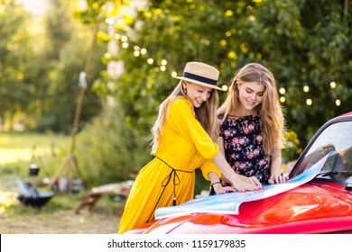 Happy pretty girls at the red car are traveling, with a map, in the camping. Unforgettable trip with friends, freedom is your way of life