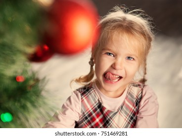 Happy Pretty little child near Christmas tree. indoor