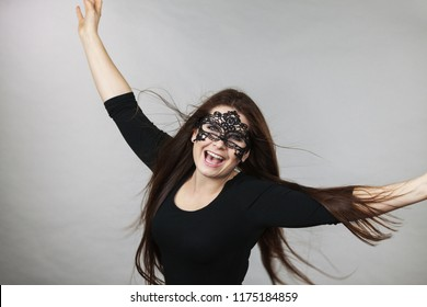 Happy pretty mysterious woman wearing black eye lace mask having tousled windblown long brown hair.