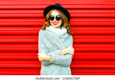 Happy pretty portrait smiling woman wearing a knitted clothes on a red background