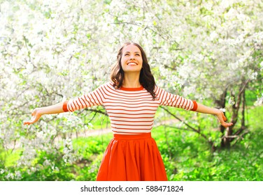 Happy pretty smiling young woman enjoying smell flowers over spring garden background