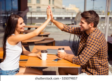 Happy pretty woman giving high five to her boyfriend in cafe
