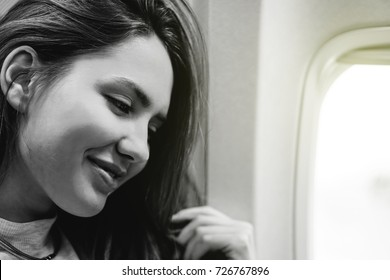 Happy pretty woman sitting in airplane next to window - Young happy girl traveling to top destinations - Vintage filter - Black and white edit