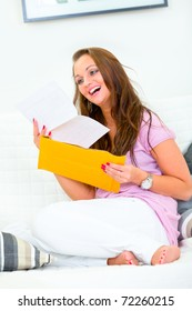 Happy pretty woman sitting on sofa at home  and reading  letter