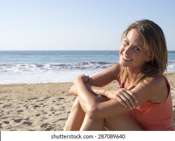happy pretty woman smiling  in the beach  wearing a pink top with the sea and horizon in the background