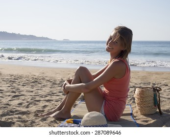 happy pretty woman smiling  in the beach  wearing a pink top, she have a beach bag, hat, a suncream,