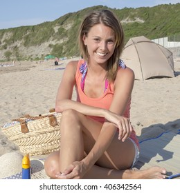 happy pretty woman smiling in the beach wearing a pink top