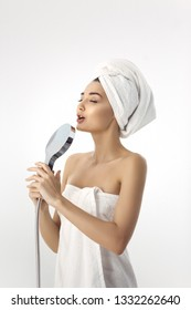 Happy pretty woman in towel singing using shower head having fun. Funny photo of cute young mixed race woman indoors in studio against white background