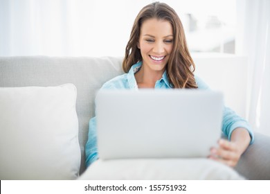 Happy pretty woman using laptop sitting on cosy sofa