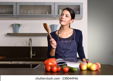 Happy Pretty Woman Wearing Apron Holding Wooden Ladle While Reading a Recipe Book at the Table with Fruits and Veggies in the Kitchen.