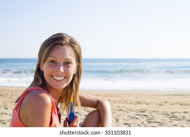 happy pretty womanl smiling  in the beach  wearing a pink top with the sea and horizon in the background