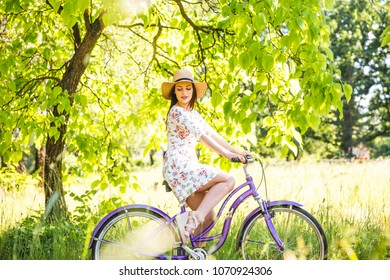 Happy pretty young girl bicycling on summer park. Happy relax time in city. Beautiful woman, sunny day.