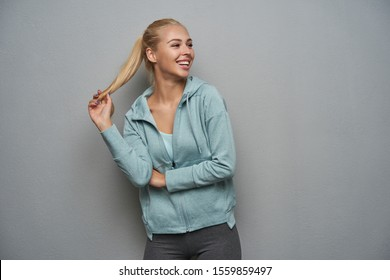 Happy pretty young sporty blonde female with ponytail hairstyle looking joyfully aside and pulling her hair, smiling broadly while standing over light grey background in sporty clothes