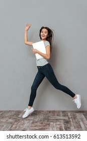 Happy pretty young woman holding laptop and running over grey background