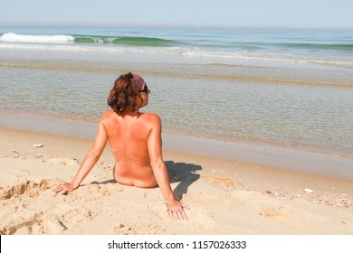 happy pretty young woman on nudist beach look side with glasses