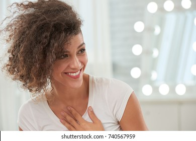Happy pretty young woman taking compliment