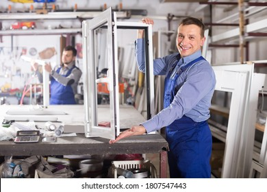 Happy production workers in coverall with different PVC windows and doors