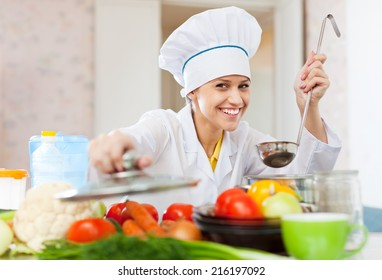Happy professional cook in white workwear works in commercial kitchen