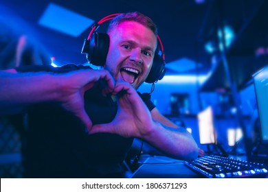 Happy professional cyber sport gamer playing online computer game with headphones, Blurred Red and Blue background.