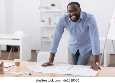Happy professional engineer leaning on the table