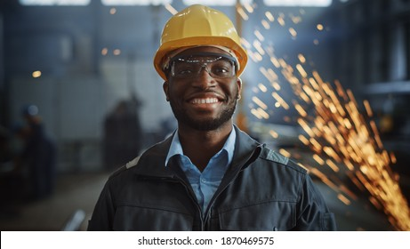 Happy Professional Heavy Industry Engineer Worker Wearing Uniform, Glasses and Hard Hat in a Steel Factory. Smiling African American Industrial Specialist Standing in a Metal Construction Manufacture.
