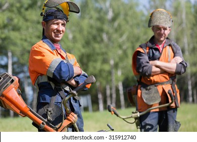 Happy professional landscapers workers with gasoline string trimmers outdoors