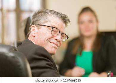 Happy professional man smiling in office with colleague