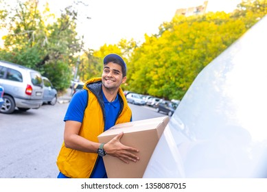 Happy professional shipping courier. Delivery postal service. Smiling young male postal delivery courier man in front of cargo van delivering package. Delivery man with cardboard boxes. delivery