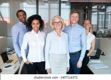 Happy professional team with old female business coach leader mentor standing posing together in office, smiling mature woman boss with diverse workers group employees looking at camera, portrait