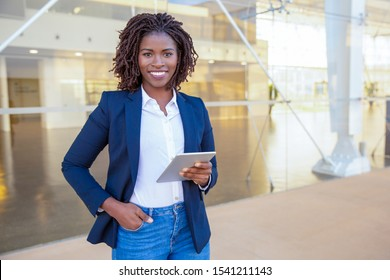 Happy professional using tablet near office building. Young African American business woman standing outside, holding digital device, looking at camera, smiling. Wi-Fi concept