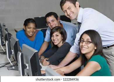 Happy professor with students working in computer lab