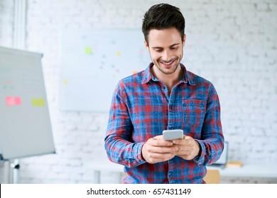 Happy programmer, web designer standing in start-up office using his smartphone