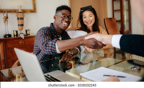 Happy property owners shaking hands with real estate broker after a deal. Young couple handshaking real estate agent after signing contract.