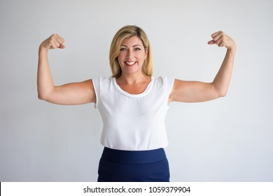 Happy proud Caucasian woman in casual wear flexing biceps. Joyful female consumer advertising food supplement or vitamins for mature women. Healthy and energy concept