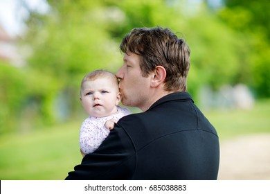 Happy proud young father having fun with newborn baby daughter, family portrait together. Dad with baby girl outdoors, love. New born child looking on dad. Bonding, family, new life