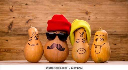 Happy pumpkin family funny faces wearing hats isolated over rustic wooden background