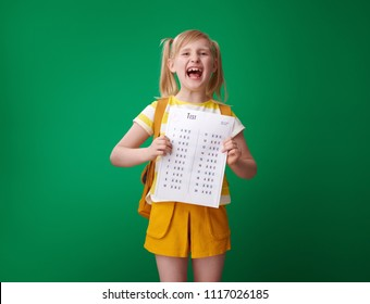 happy pupil with backpack holding an excellent grade test isolated on green