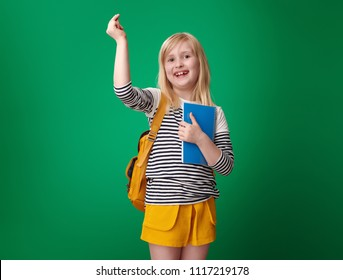happy pupil with backpack snapping with fingers isolated on green