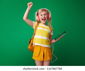 happy pupil with backpack with tablet PC and headphones rejoicing isolated on green
