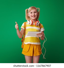 happy pupil with backpack with tablet PC and headphones showing thumbs up on green background