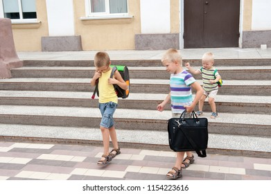 Happy pupil children go back to school. Start new education year after vacation. Boys and his little brother with bags are playing near school building. Education for kindergarten and preschool kids