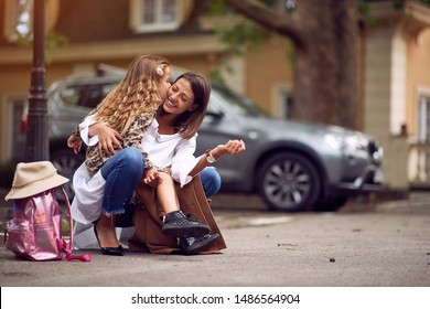 happy pupil girl and mother after first day of school is over,