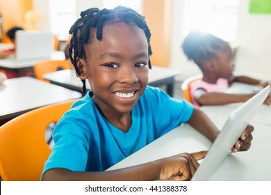 Happy pupil using tablet pc in classroom at elementary school