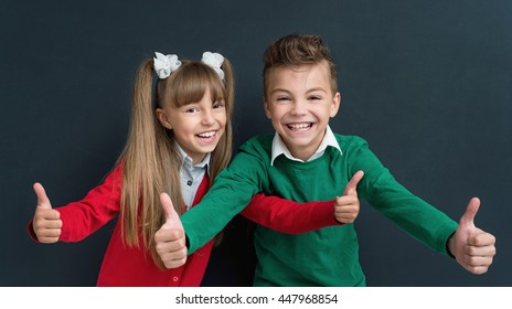 Happy pupils - boy and girl, showing thumbs up gesture in front of a big chalkboard. Back to school concept.